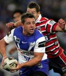 SYDNEY, AUSTRALIA - JULY 02:  Adam Perry of the Bulldogs is about to offload the ball during the round 16 NRL match between the Bulldogs and the Sydney Rooster at Telstra Stadium on July 2, 2007 in Sydney, Australia.  (Photo by Robert Gray/Getty Images)